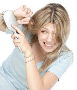 Beautiful young woman combing her hair